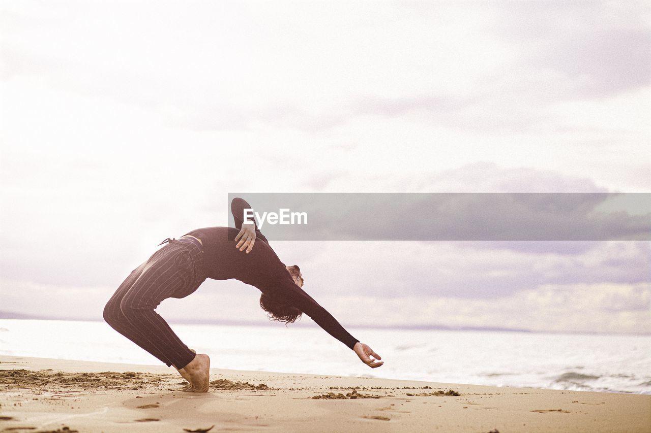 Full length of man dancing in the beach
