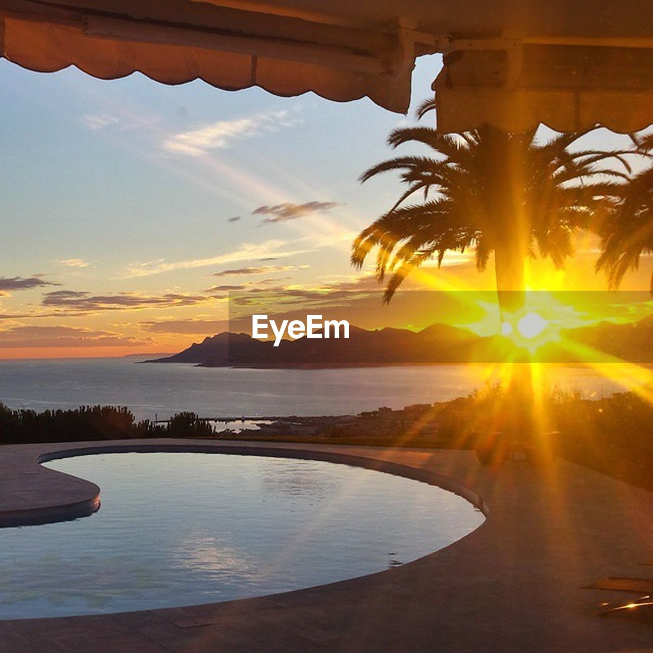 sunset, water, sky, beauty in nature, scenics - nature, tranquil scene, tree, palm tree, reflection, nature, tranquility, no people, cloud - sky, sea, orange color, tropical climate, sun, non-urban scene, idyllic, swimming pool, lens flare