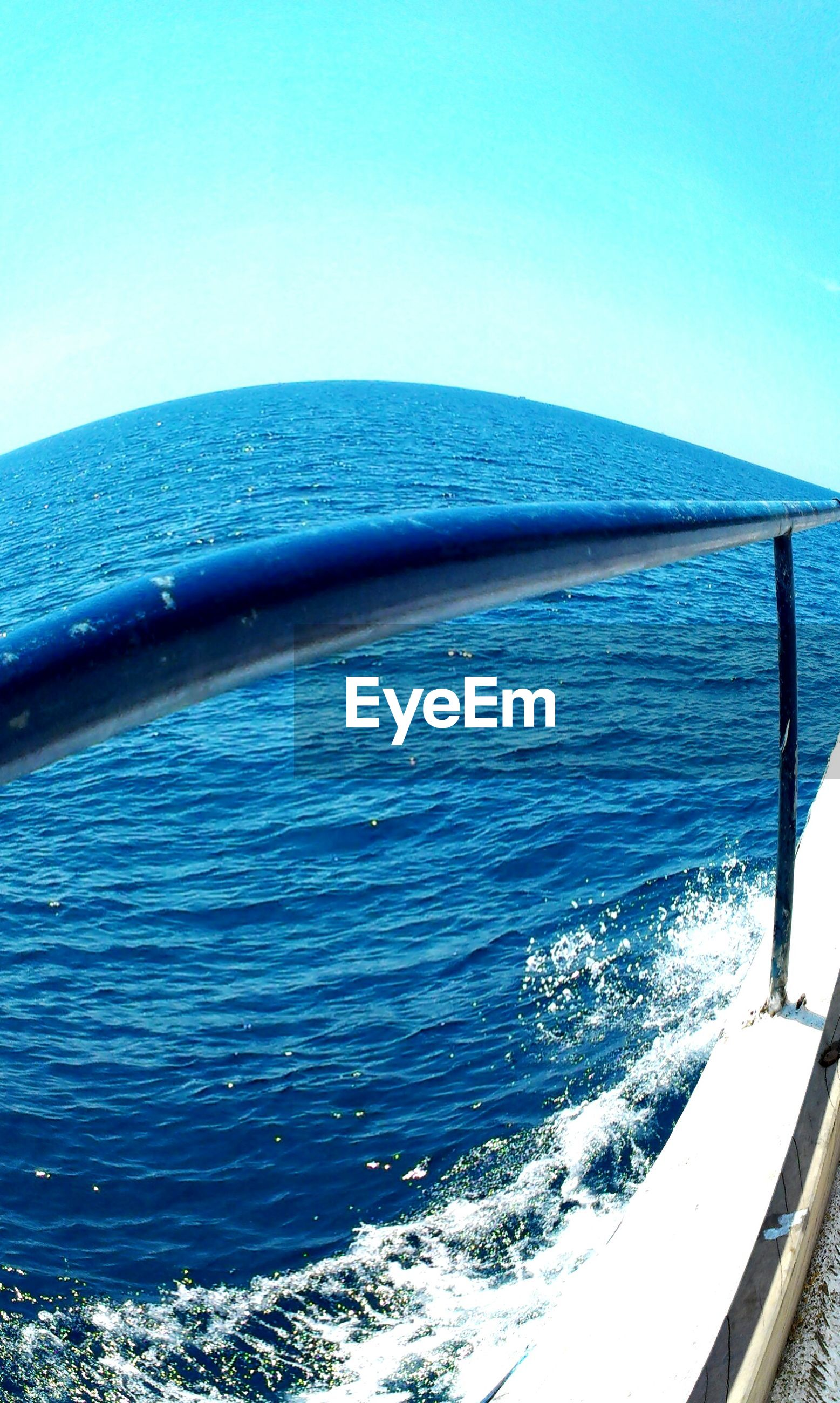 Fish-eye lens of sea and boat railing against clear sky