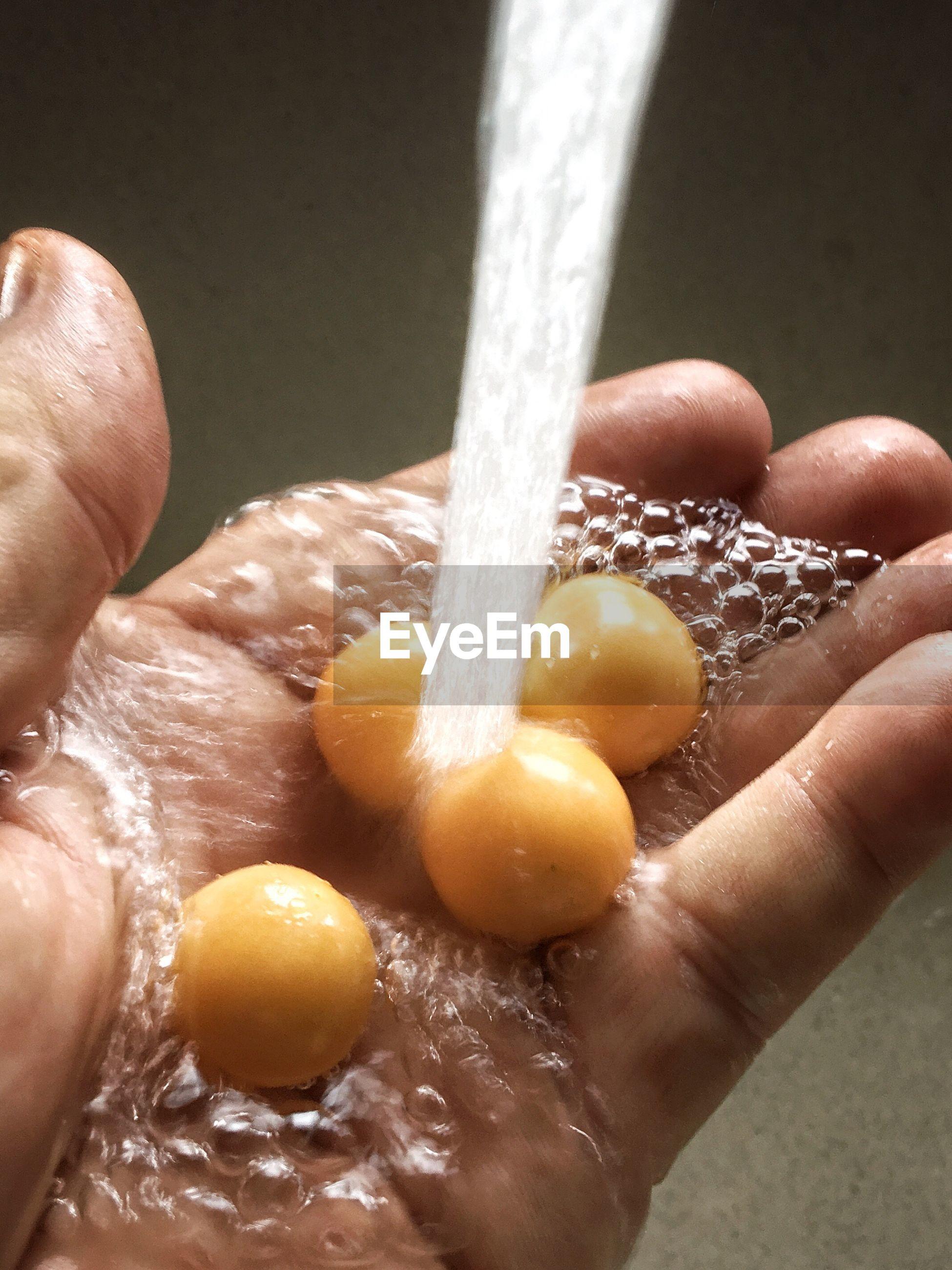 Close-up of human hand washing food under running water