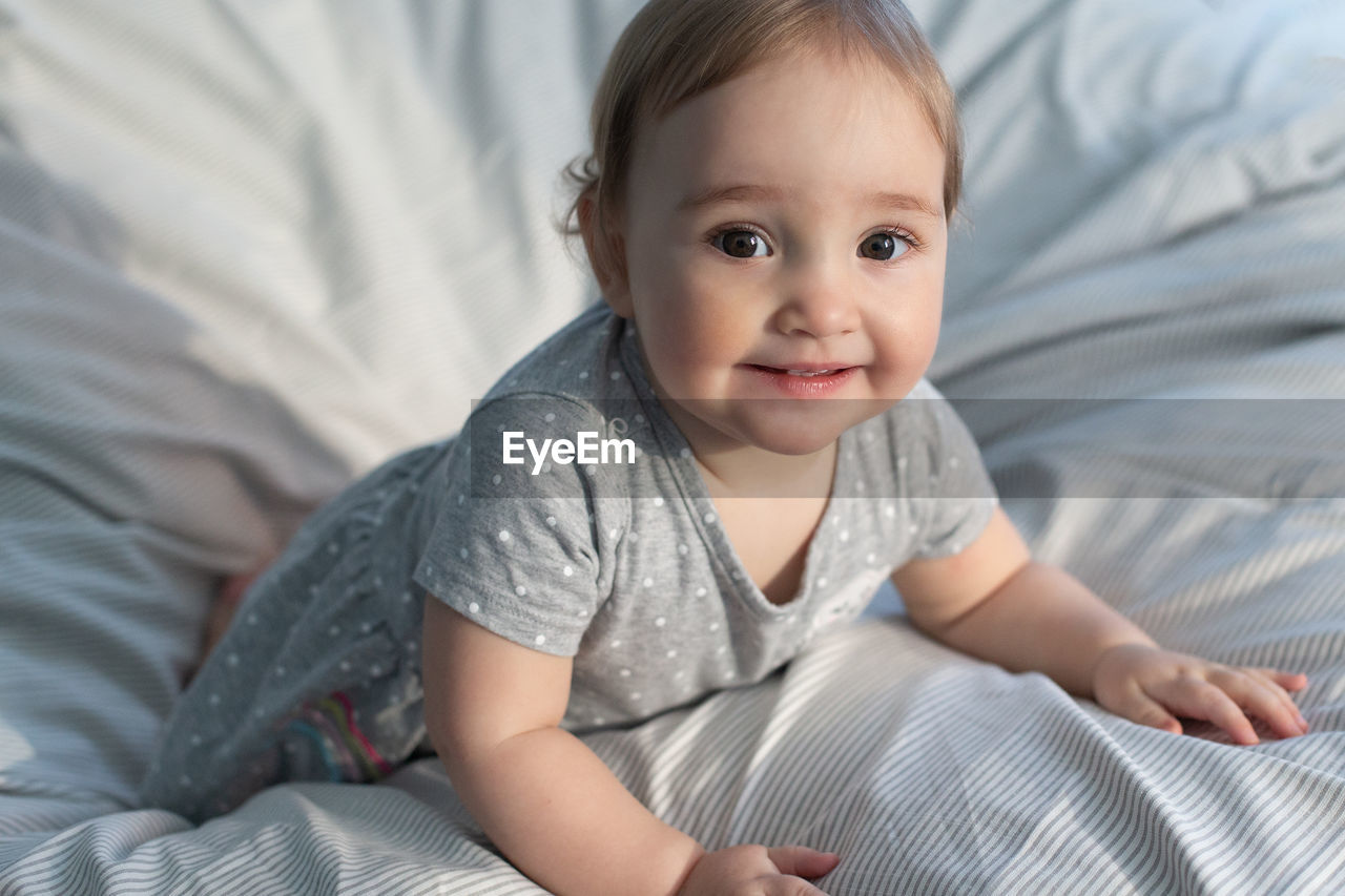 Cute smiling baby girl laying in the bed in morning sun light. grey colors