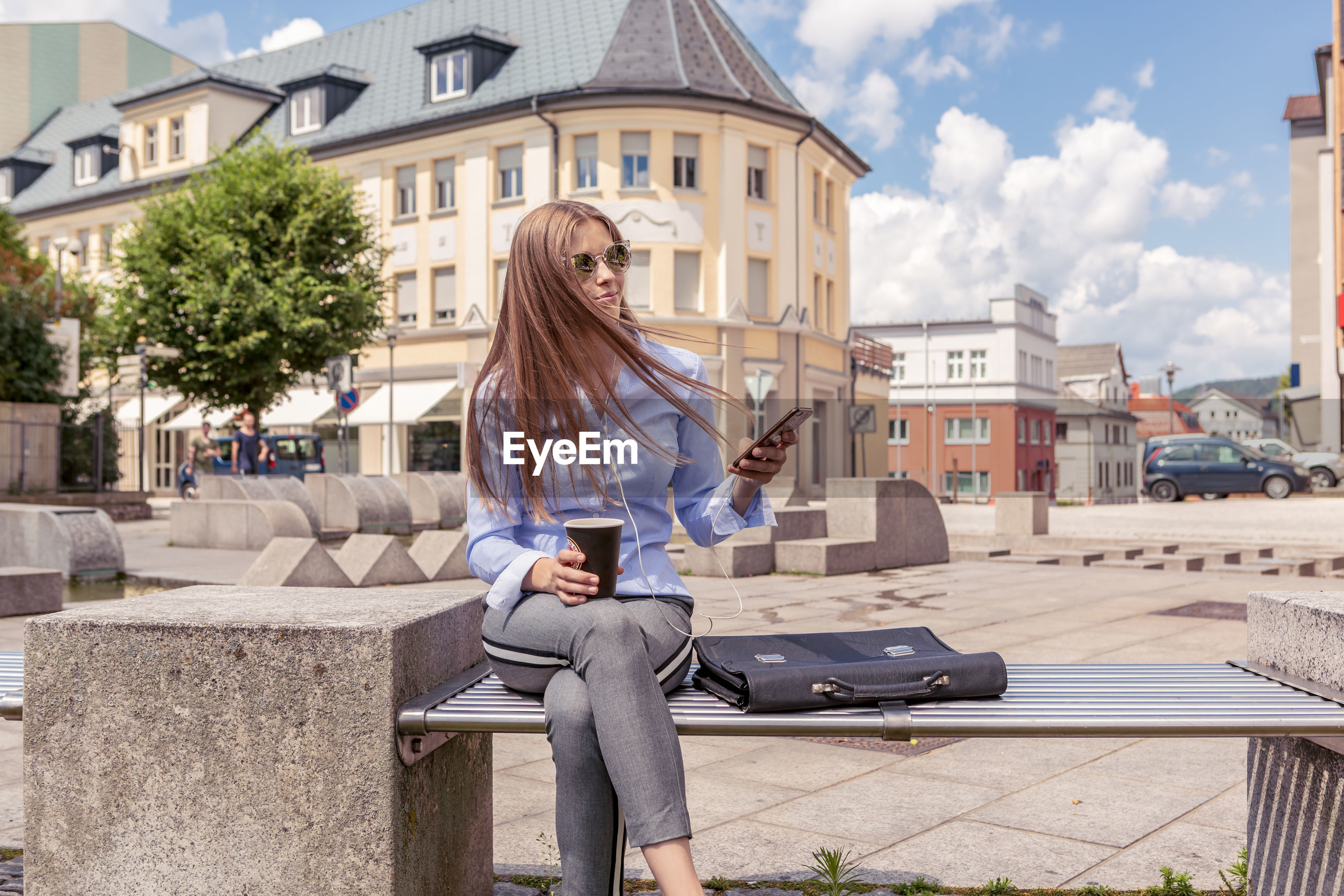 Young woman holding phone while sitting on bench against building