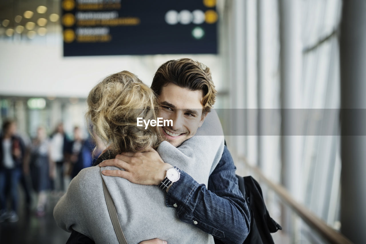 Happy businessman embracing female colleague at airport