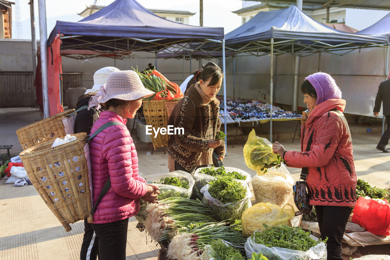 retail, real people, women, selling, group of people, food, food and drink, vegetable, clothing, market, hat, people, adult, healthy eating, day, container, occupation, men, basket, small business, outdoors, buying, retail display, sale