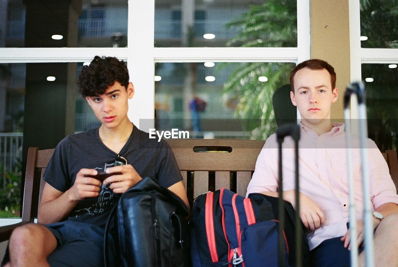 young adult, two people, sitting, young men, front view, mobile phone, wireless technology, communication, people, looking, looking away, technology, real people, casual clothing, young women, lifestyles, three quarter length, waist up, focus on foreground, outdoors, couple - relationship, teenager, contemplation, adolescence