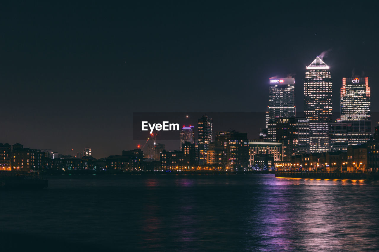 building exterior, illuminated, architecture, night, city, skyscraper, built structure, cityscape, waterfront, tall - high, urban skyline, water, travel destinations, river, tower, modern, sky, no people, tourism, downtown district, travel, outdoors, clear sky, nautical vessel, nature