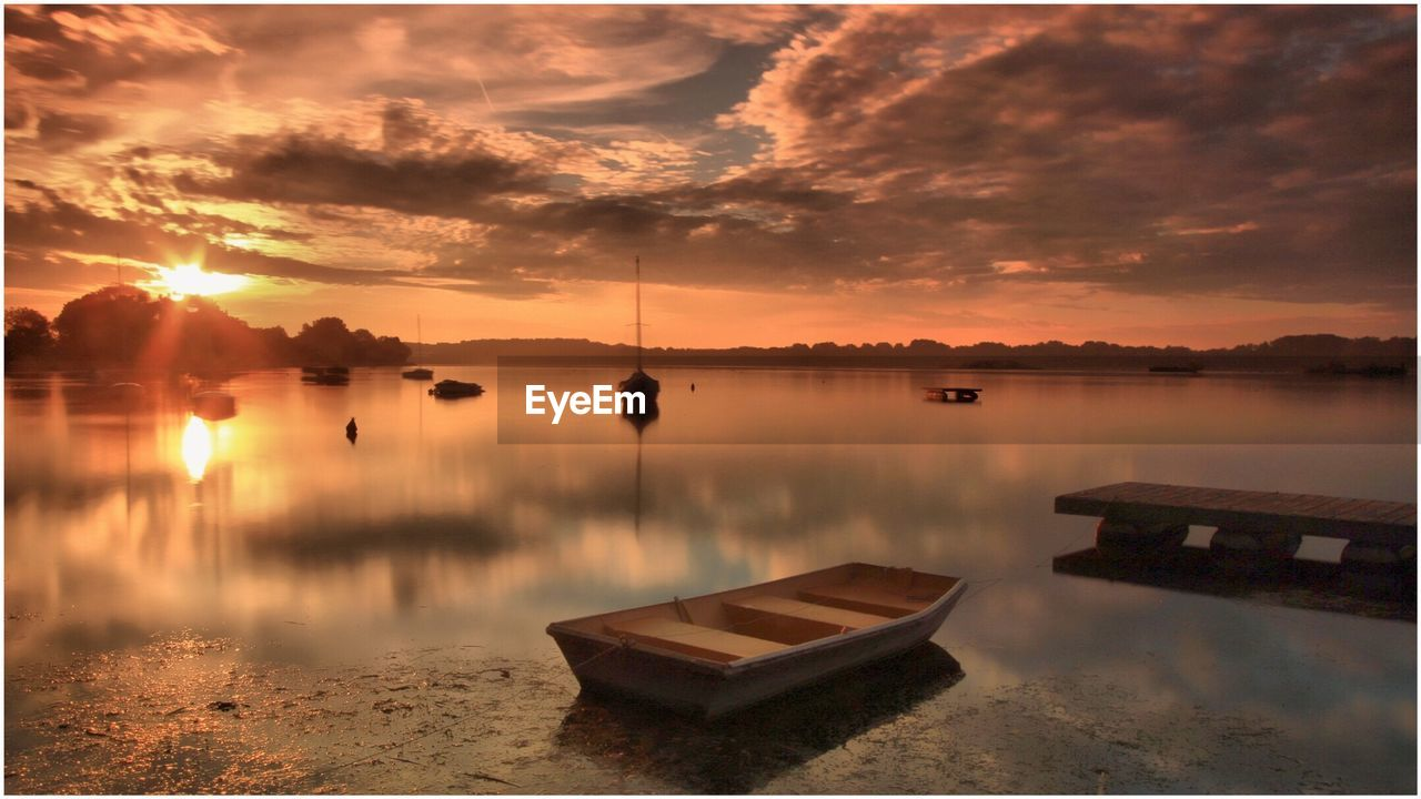 Boats Moored At Riverbank Against Sky During Sunset