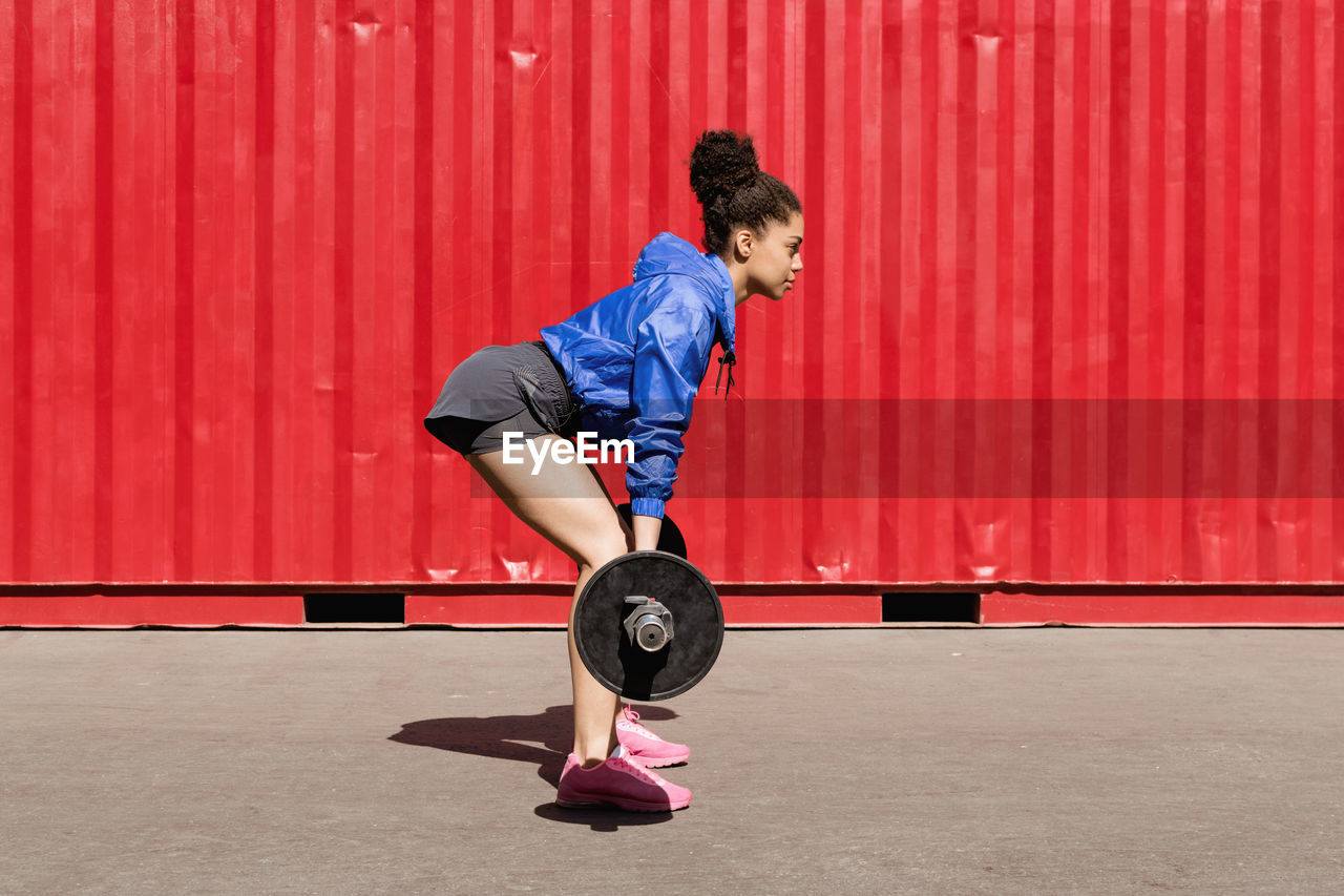 Side View Of Young Woman Lifting Barbell By Red Cargo Container