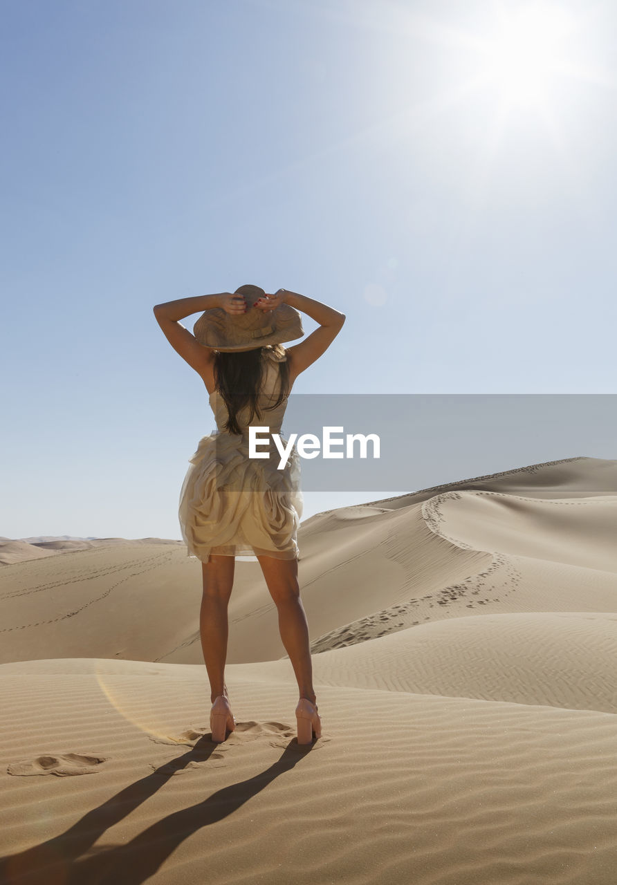Full Length Of Woman Standing On Sand At Beach Against Clear Sky
