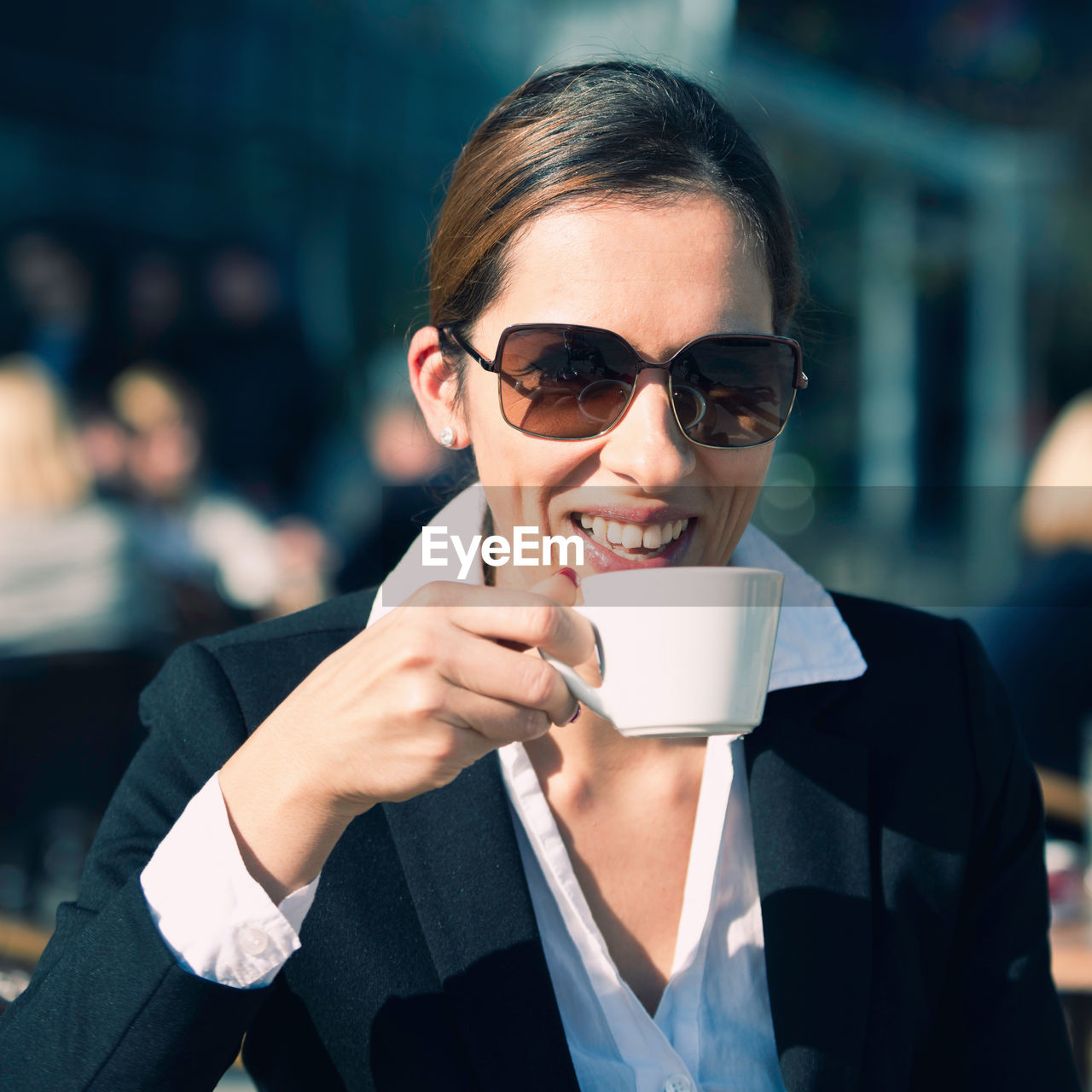 Smiling businesswoman drinking coffee while sitting at sidewalk cafe