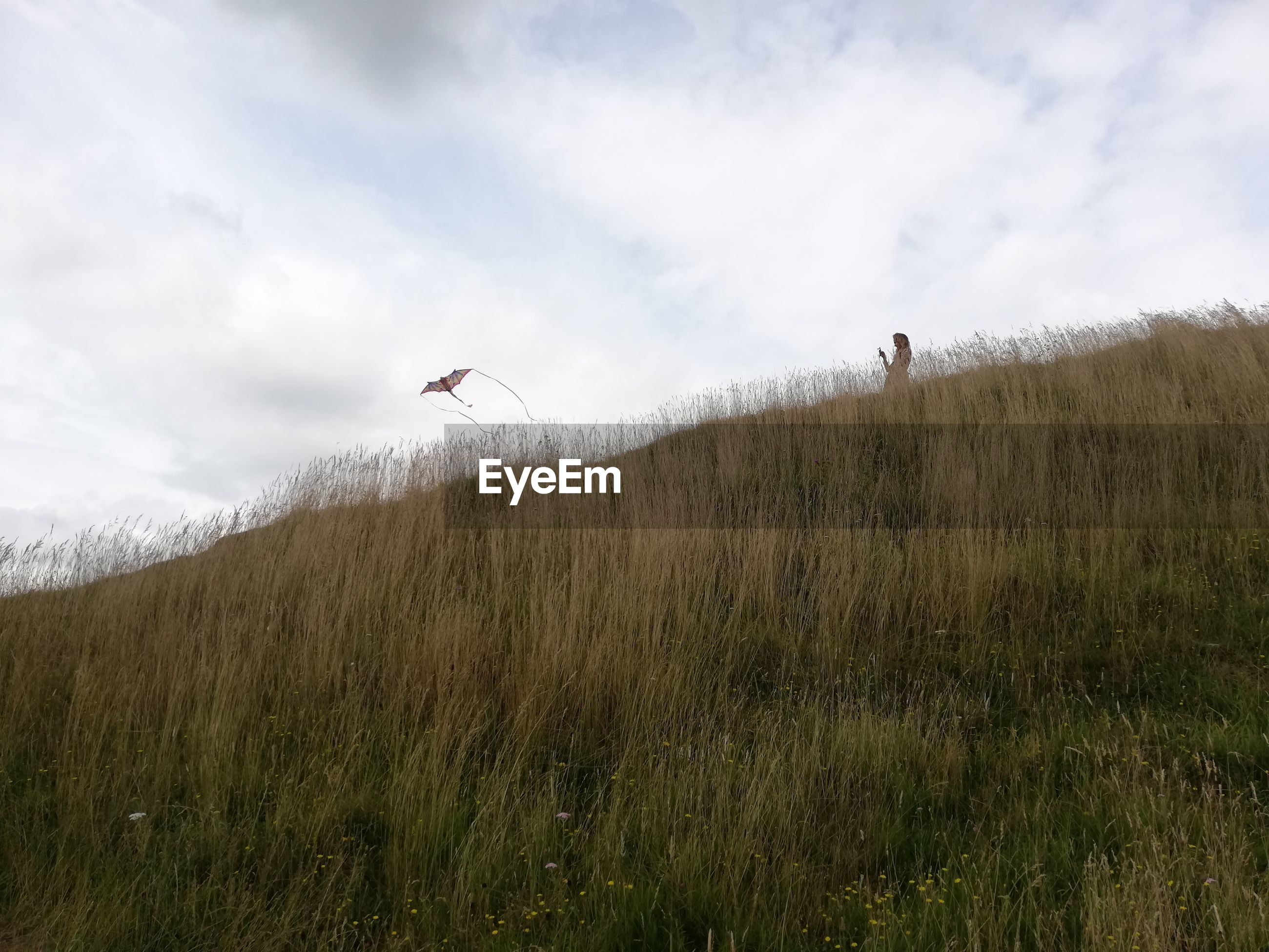 Low angle view of woman flying kite while standing on mountain
