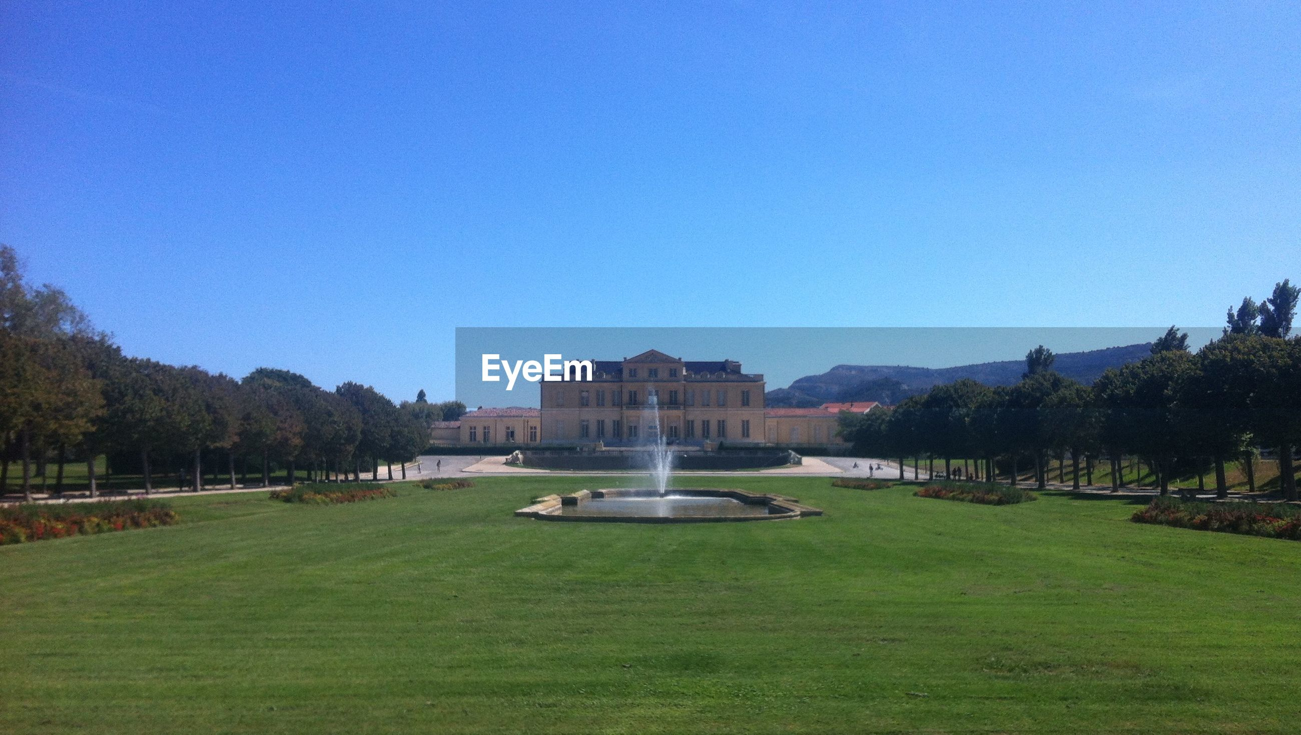 Fountain at lawn in front of building against clear sky