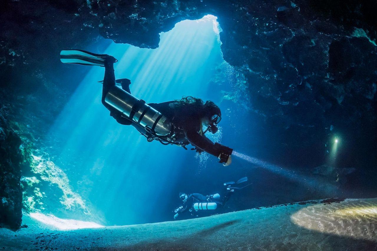 People With Flashlight Swimming In Sea