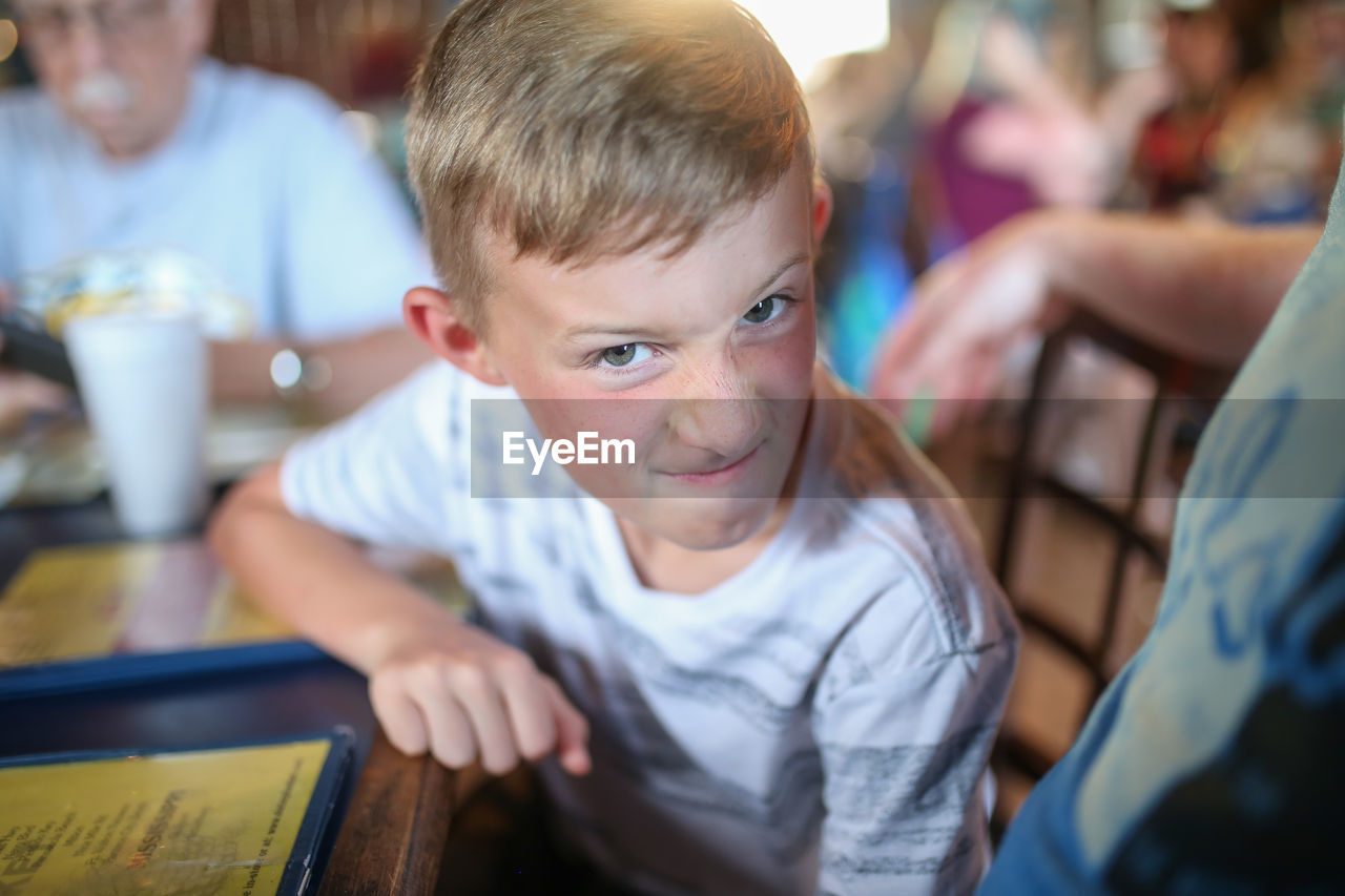 Portrait of angry boy sitting at restaurant