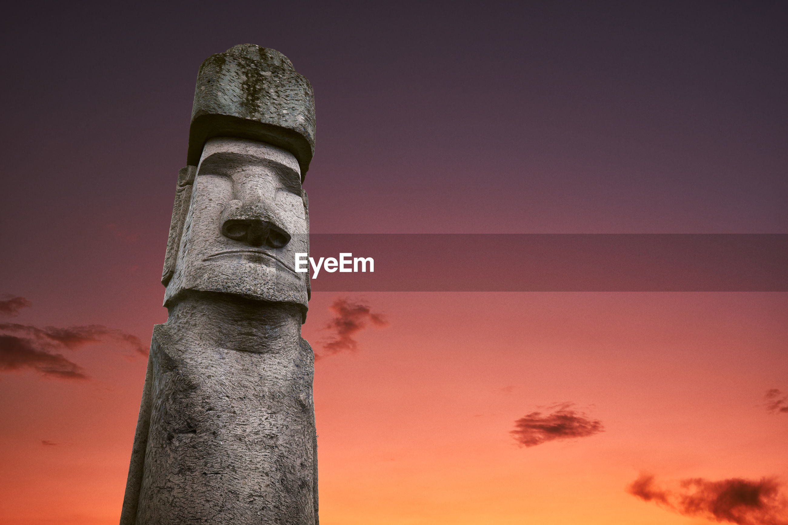An ancient moai statue at easter island and rapa nui civilization at sunset with clouds