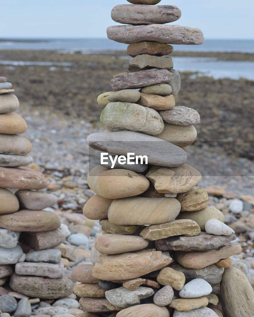 sea, stack, balance, pebble, water, rock - object, day, large group of objects, outdoors, no people, focus on foreground, beach, nature, horizon over water, close-up, beauty in nature, sky, pebble beach