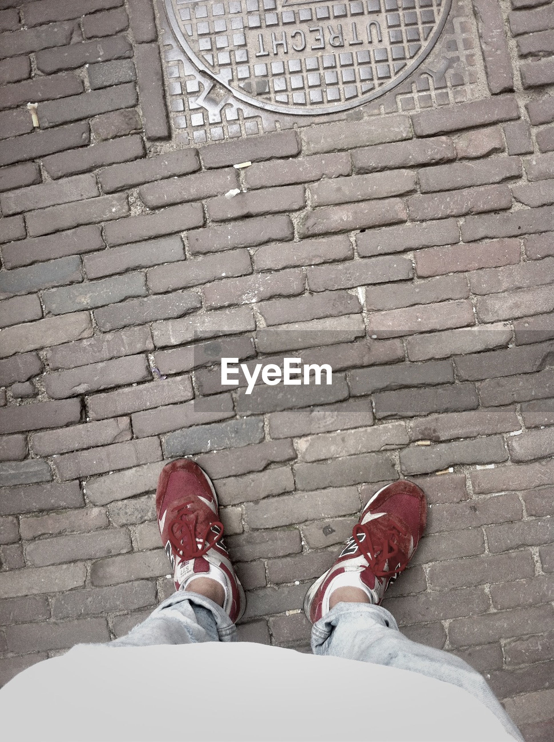 low section, person, shoe, standing, lifestyles, personal perspective, human foot, leisure activity, cobblestone, high angle view, men, paving stone, footwear, red, casual clothing, footpath