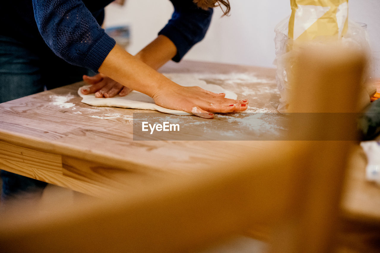 food and drink, selective focus, human hand, indoors, food, real people, dough, hand, wood - material, preparation, table, freshness, flour, rolling pin, human body part, pasta, italian food, one person, preparing food, midsection, kneading