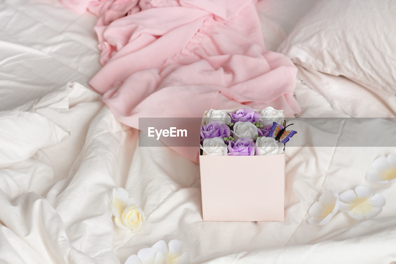 HIGH ANGLE VIEW OF FLOWER PETALS ON BED