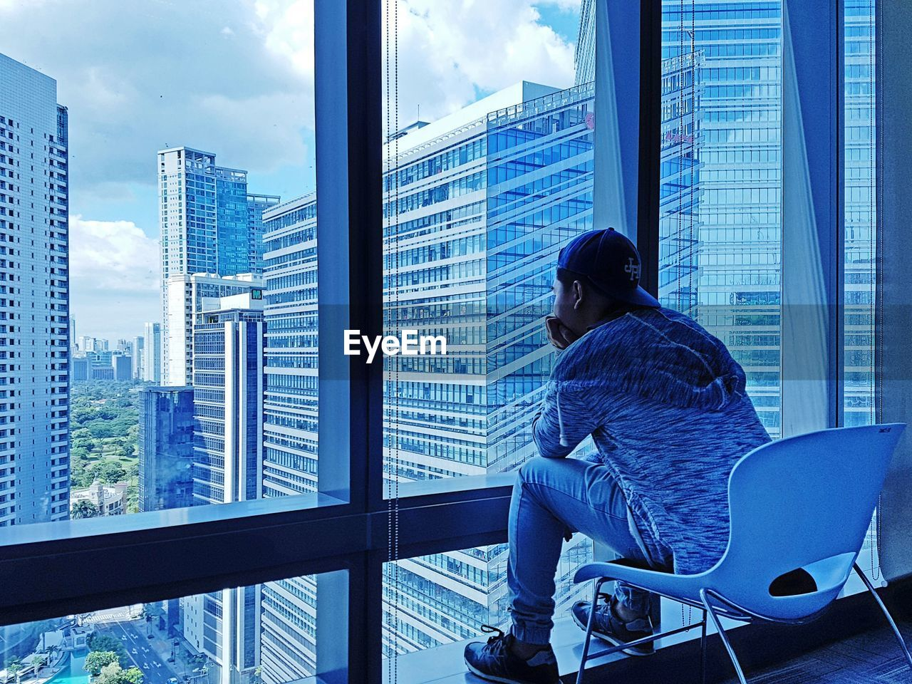 skyscraper, one person, window, architecture, built structure, real people, indoors, day, casual clothing, women, city, full length, building exterior, blinds, lifestyles, cityscape, young adult, sky, adult, people