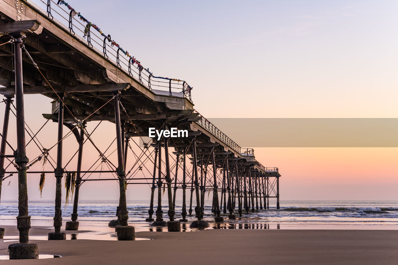 sky, water, sea, built structure, architecture, beach, land, sunset, nature, no people, horizon, scenics - nature, pier, horizon over water, tranquility, beauty in nature, tranquil scene, outdoors, clear sky, architectural column