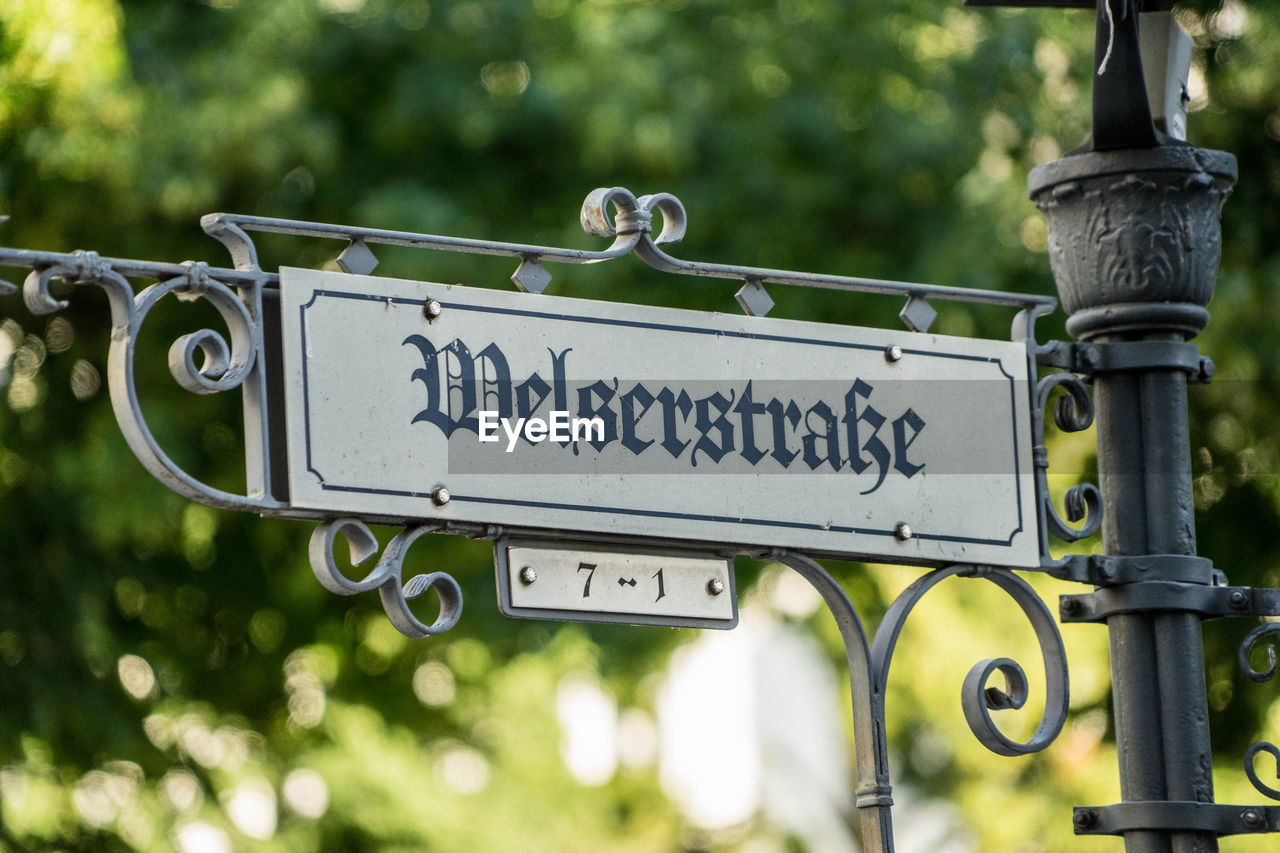 text, communication, sign, western script, metal, focus on foreground, no people, information, day, information sign, guidance, close-up, outdoors, nature, road, plant, road sign, tree, low angle view, direction
