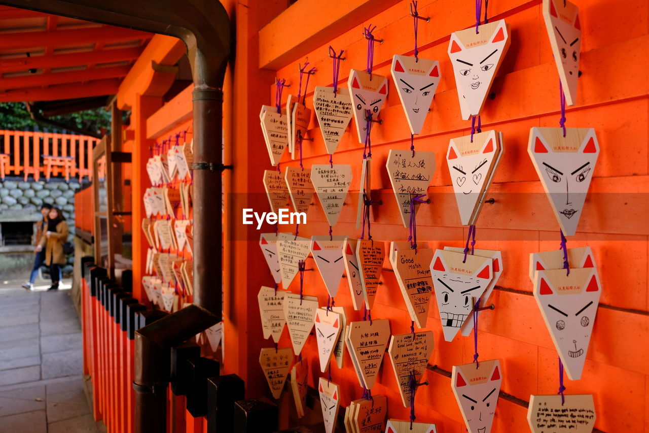 non-western script, text, communication, large group of objects, script, orange color, built structure, hanging, building, place of worship, no people, spirituality, religion, architecture, belief, in a row, wall - building feature, abundance, day, outdoors, shrine