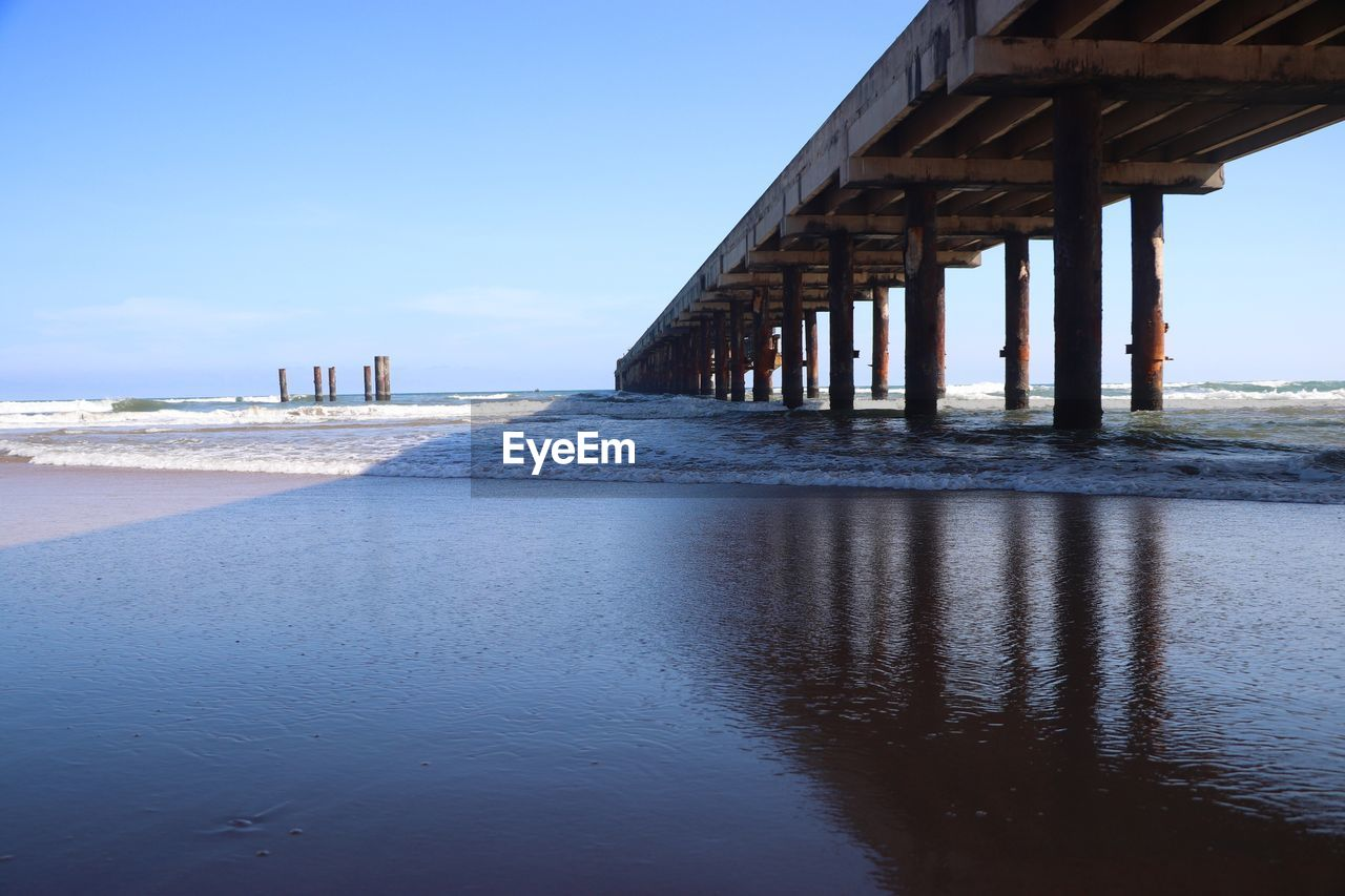 sea, beach, water, architecture, built structure, sand, day, nature, outdoors, bridge - man made structure, scenics, no people, beauty in nature, wave, sky, horizon over water, underneath