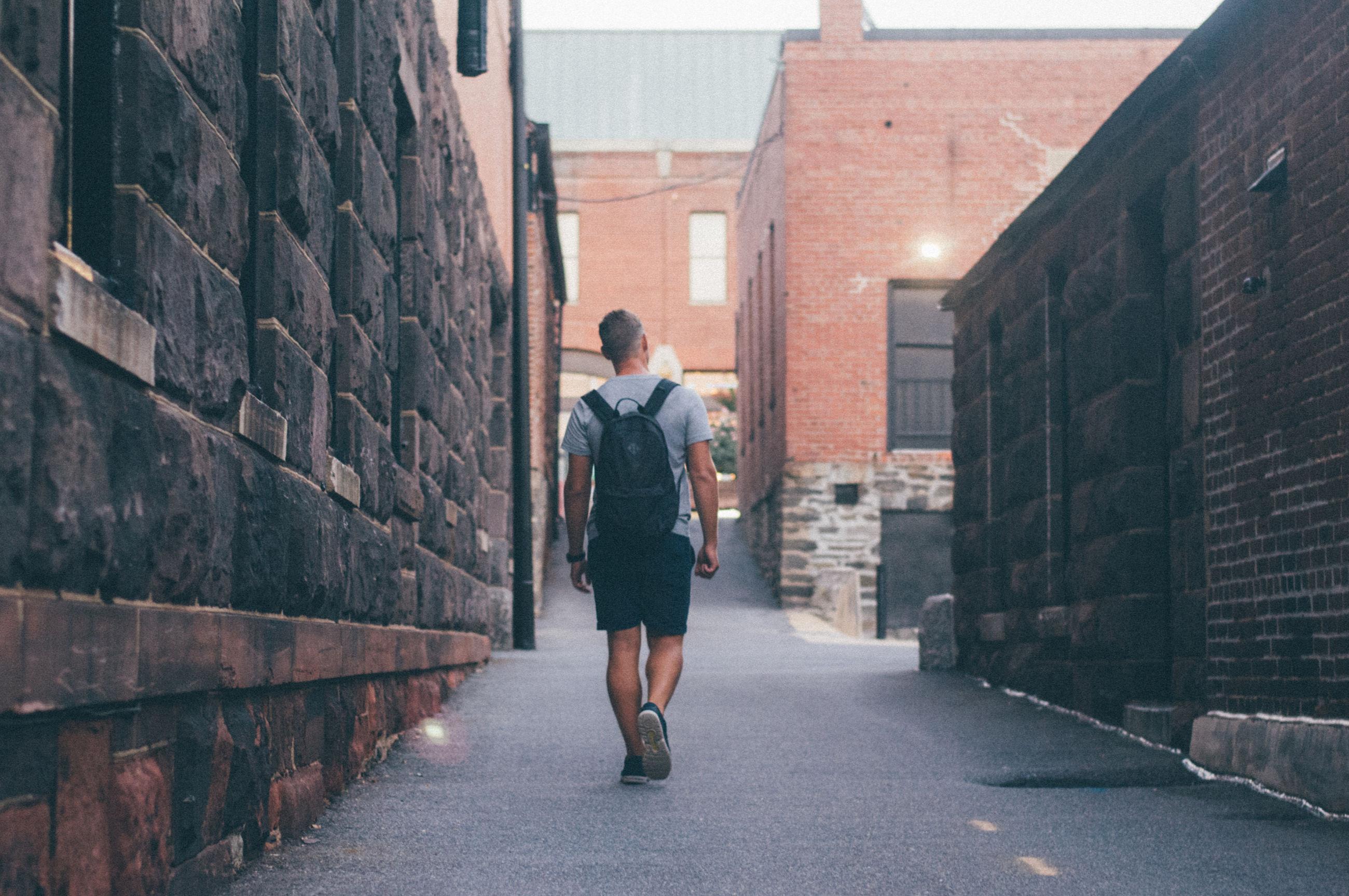 FULL LENGTH REAR VIEW OF MAN WALKING ON STREET AMIDST BUILDINGS