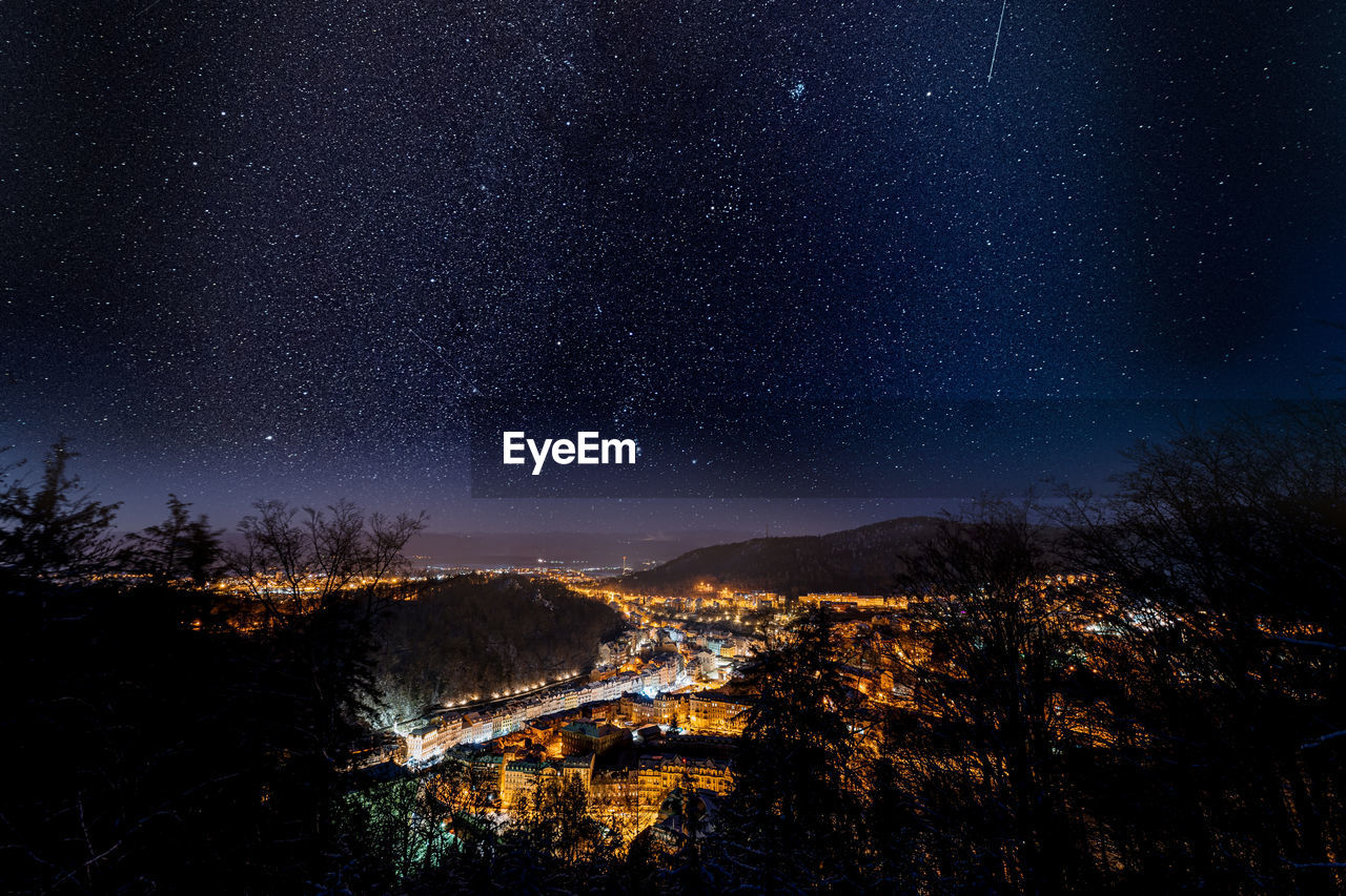 Aerial view of illuminated town against sky at night
