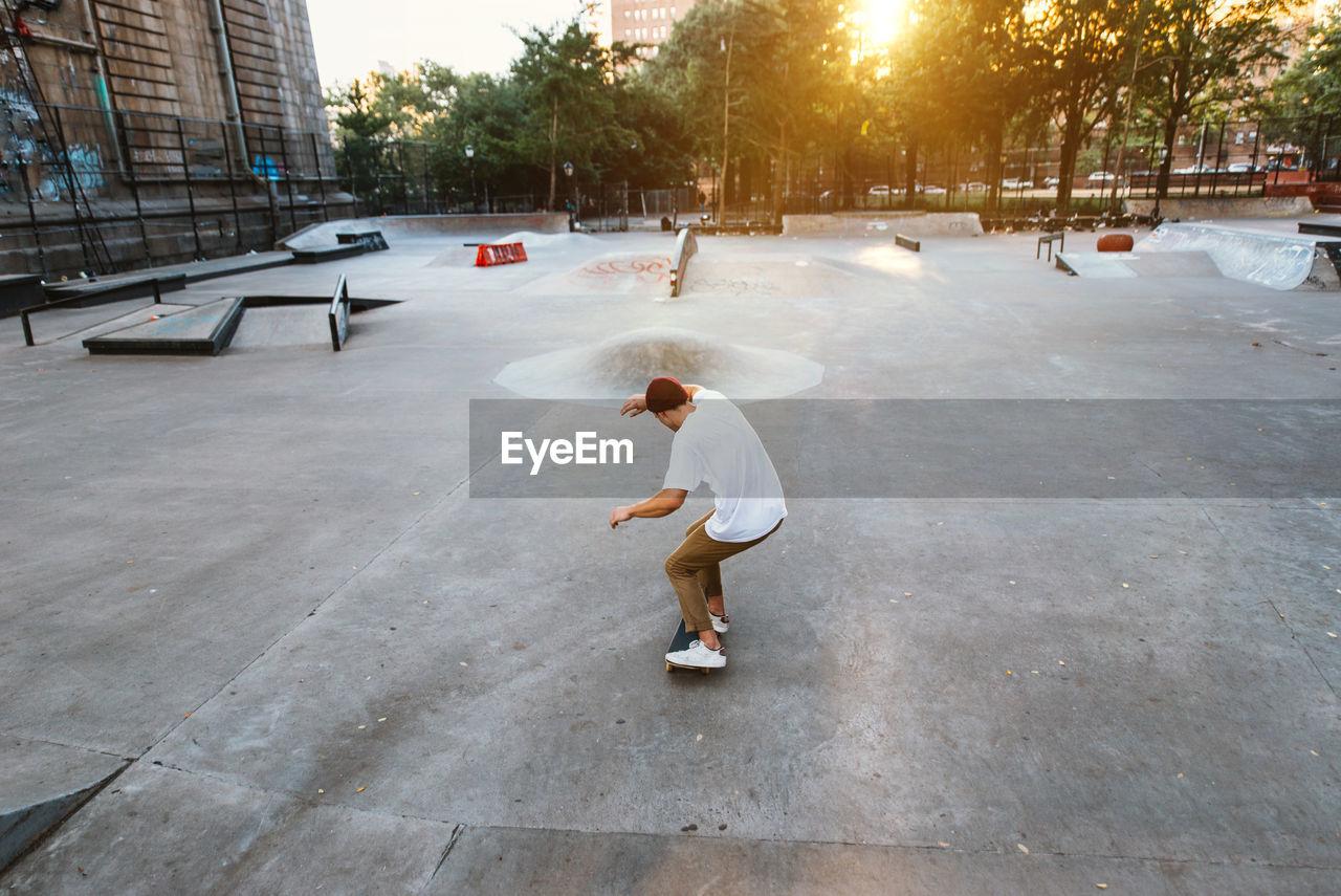 Full length of man skateboarding at skating park against building