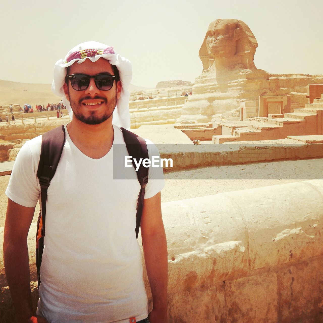 Portrait Of Smiling Man In Sunglasses Standing Against Sphinx Of Giza