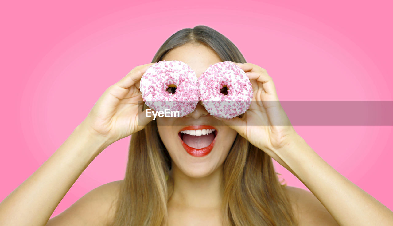 Young woman with eyes covered by donuts against pink background