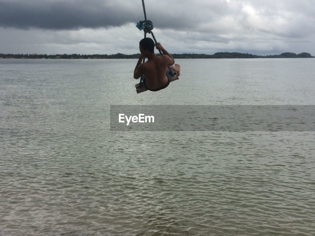 Rear View Of Swinging Over Sea