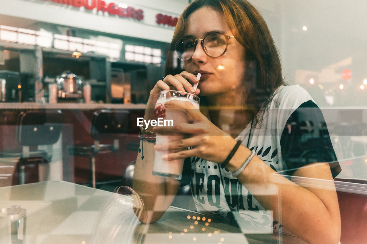 one person, real people, young adult, women, lifestyles, food and drink, indoors, restaurant, leisure activity, portrait, young women, cafe, adult, business, front view, dessert, hairstyle, headshot, sweet food, hair, glass