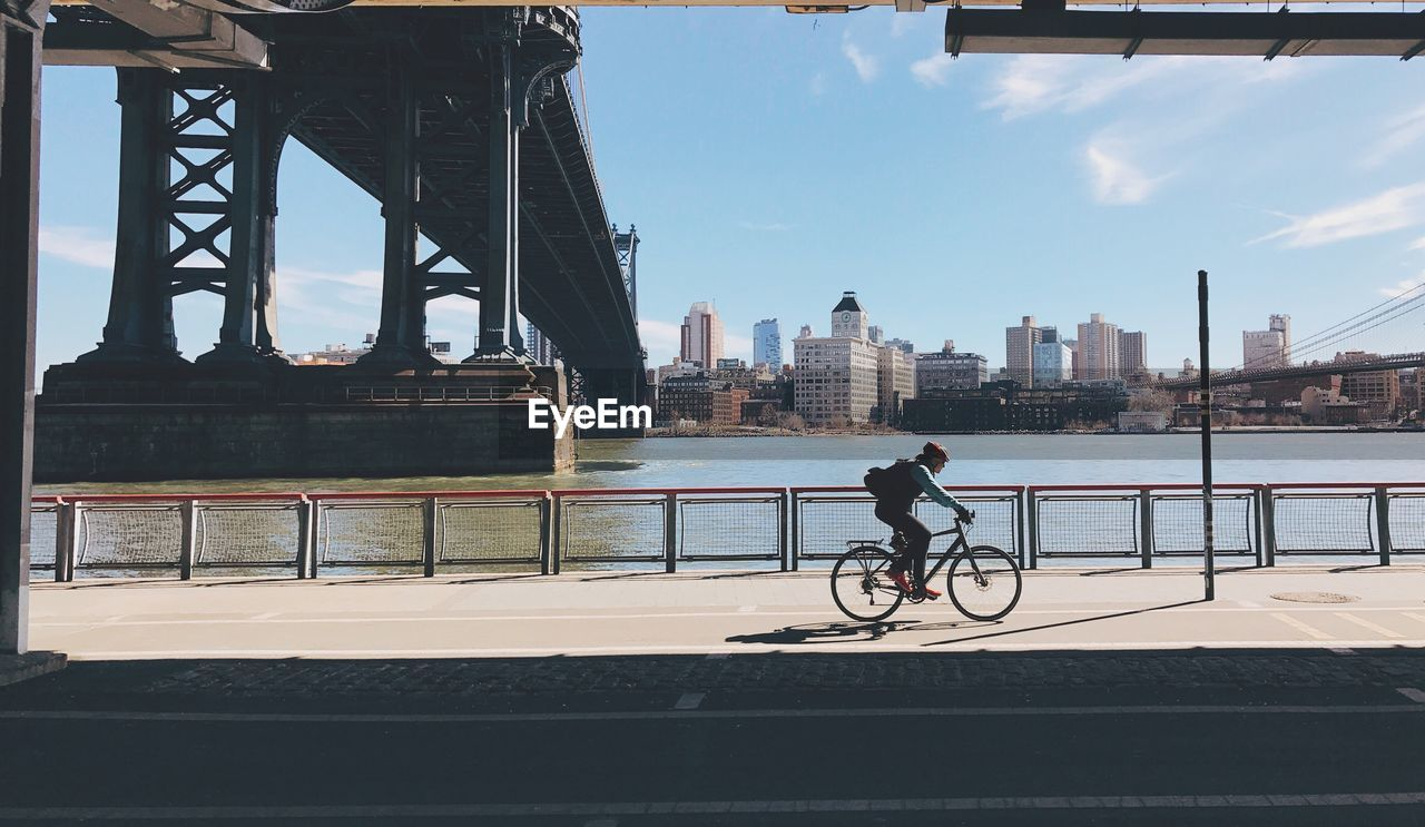 MAN WITH BICYCLE ON RIVERBANK