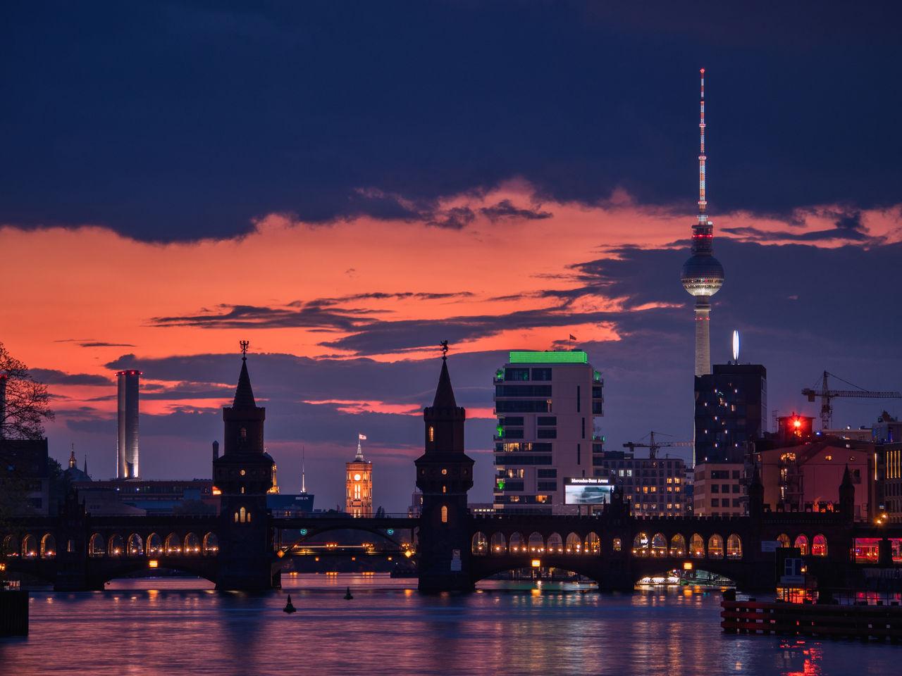 Illuminated bridge over river against buildings in city against at dusk
