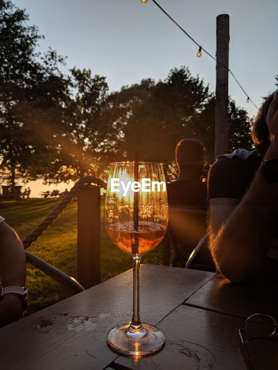 PEOPLE SITTING AT RESTAURANT BY GLASS DURING SUNSET