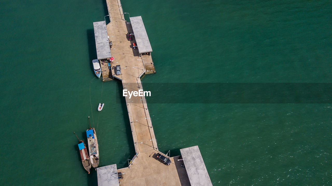water, high angle view, sea, day, nature, real people, transportation, architecture, outdoors, nautical vessel, built structure, leisure activity, lifestyles, turquoise colored, waterfront, men, people, green color, sunlight