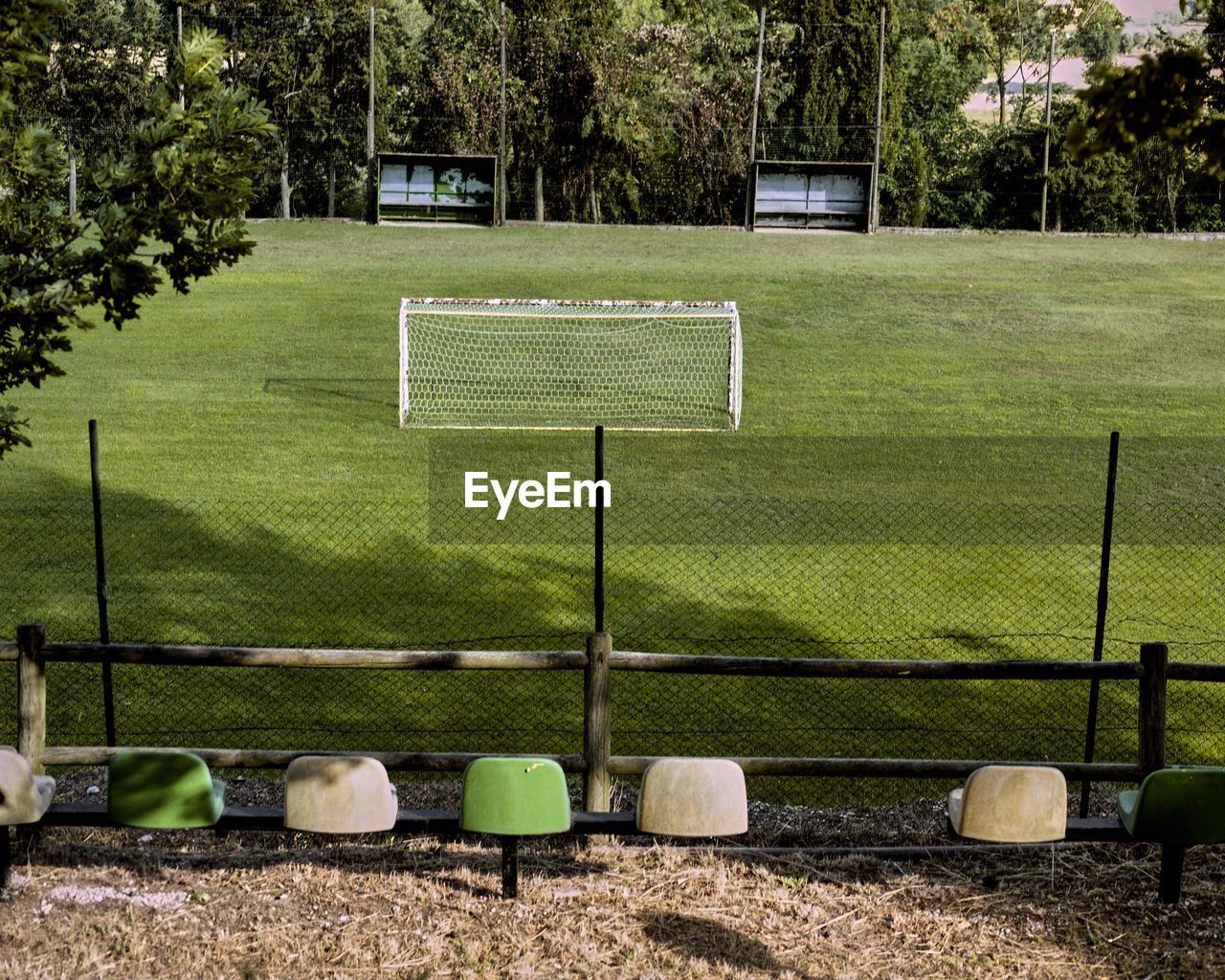 plant, grass, nature, sport, absence, day, soccer field, no people, outdoors, green color, land, tree, soccer, playing field, team sport, empty, fence, architecture, tranquility, sunlight