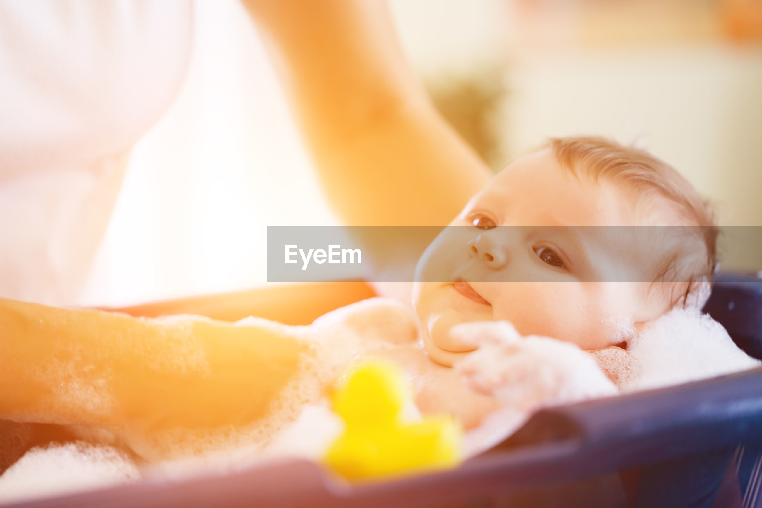 Midsection of mother bathing daughter in baby tub