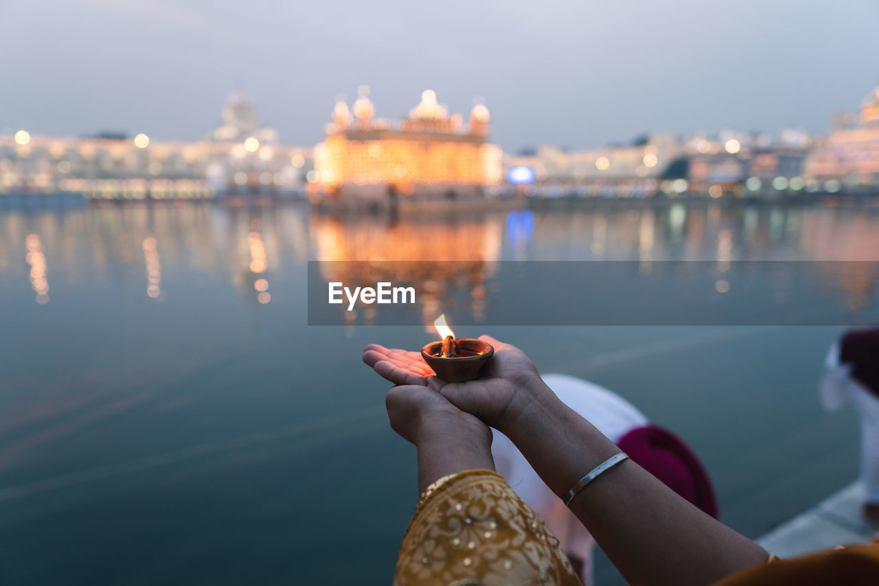 Holding diya against the golden temple during diwali