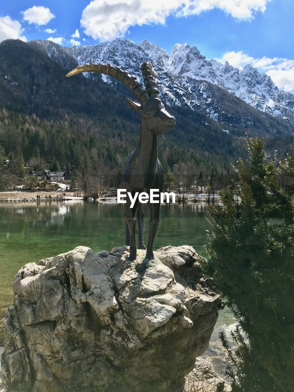Statue on rock against lake
