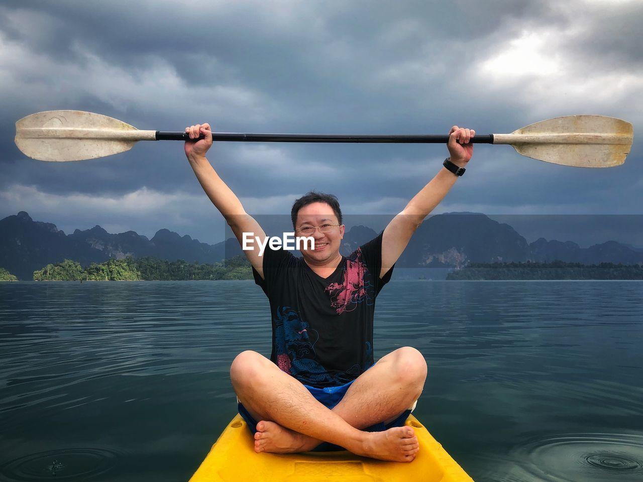 Portrait of smiling man kayaking in lake against sky