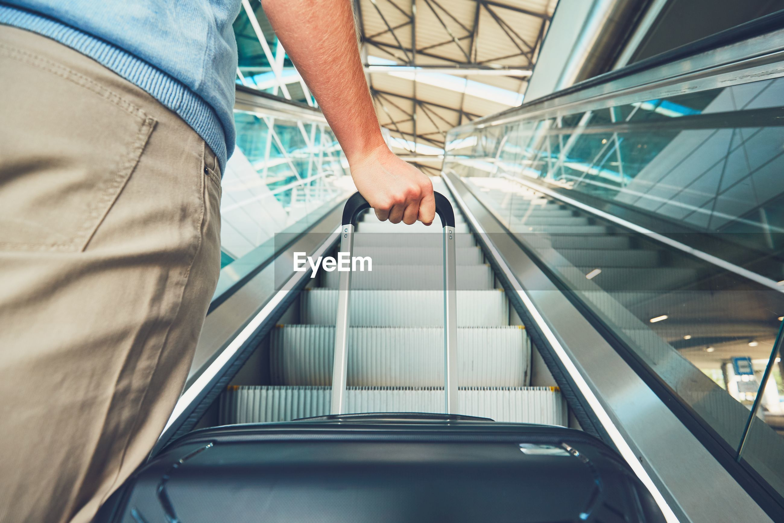 Cropped image of man holding luggage on escalator at airport