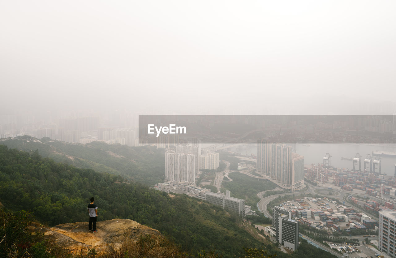 High Angle View Of Man Looking At Cityscape While Standing On Mountain During Foggy Weather