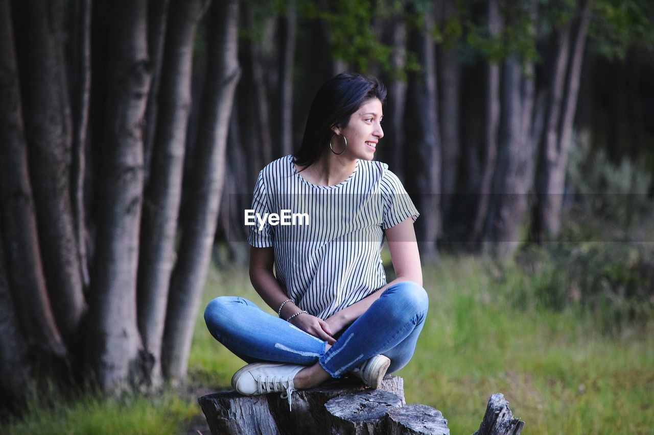 Full length of woman sitting on tree stump in forest