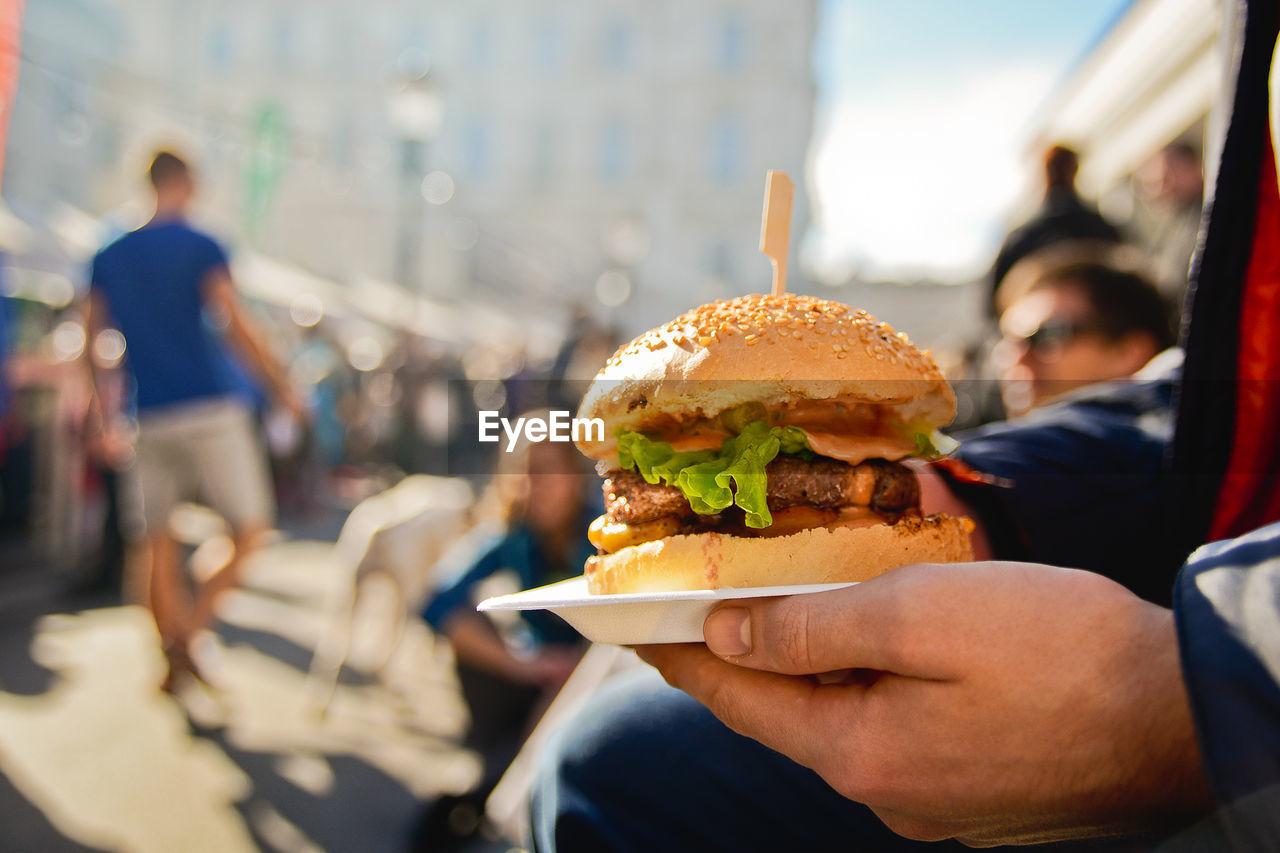 Close-Up Of Man Holding Burger