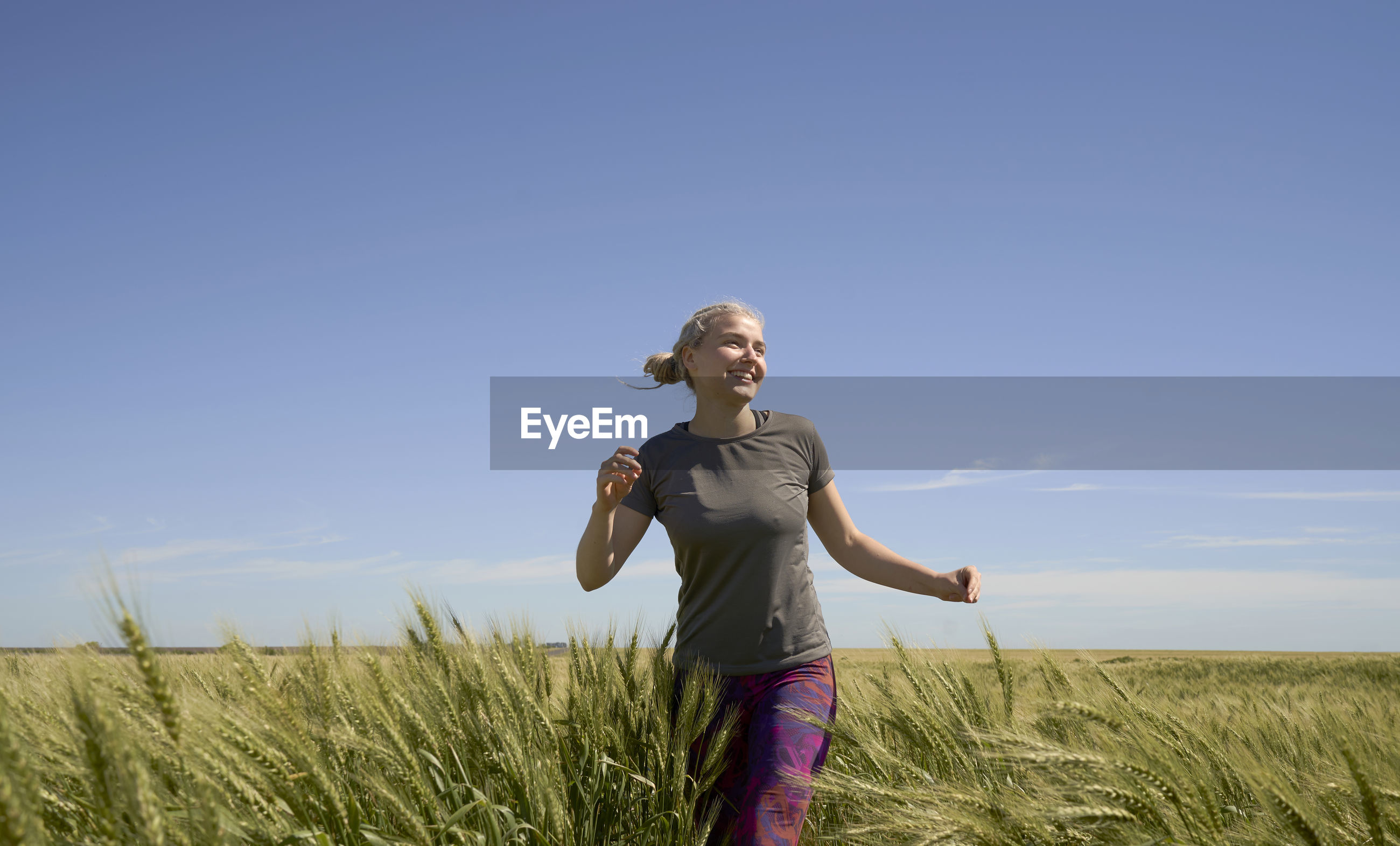 Young european latin woman running in wheat field