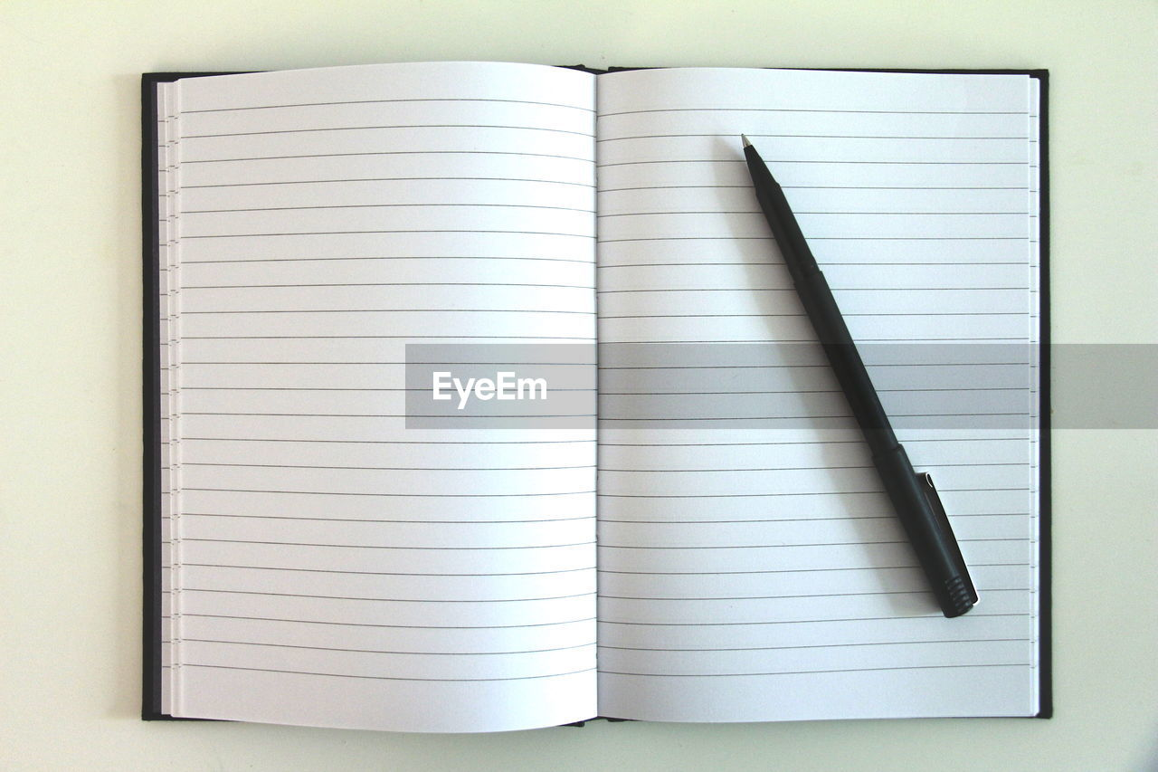 Directly above shot of open book with pen on table
